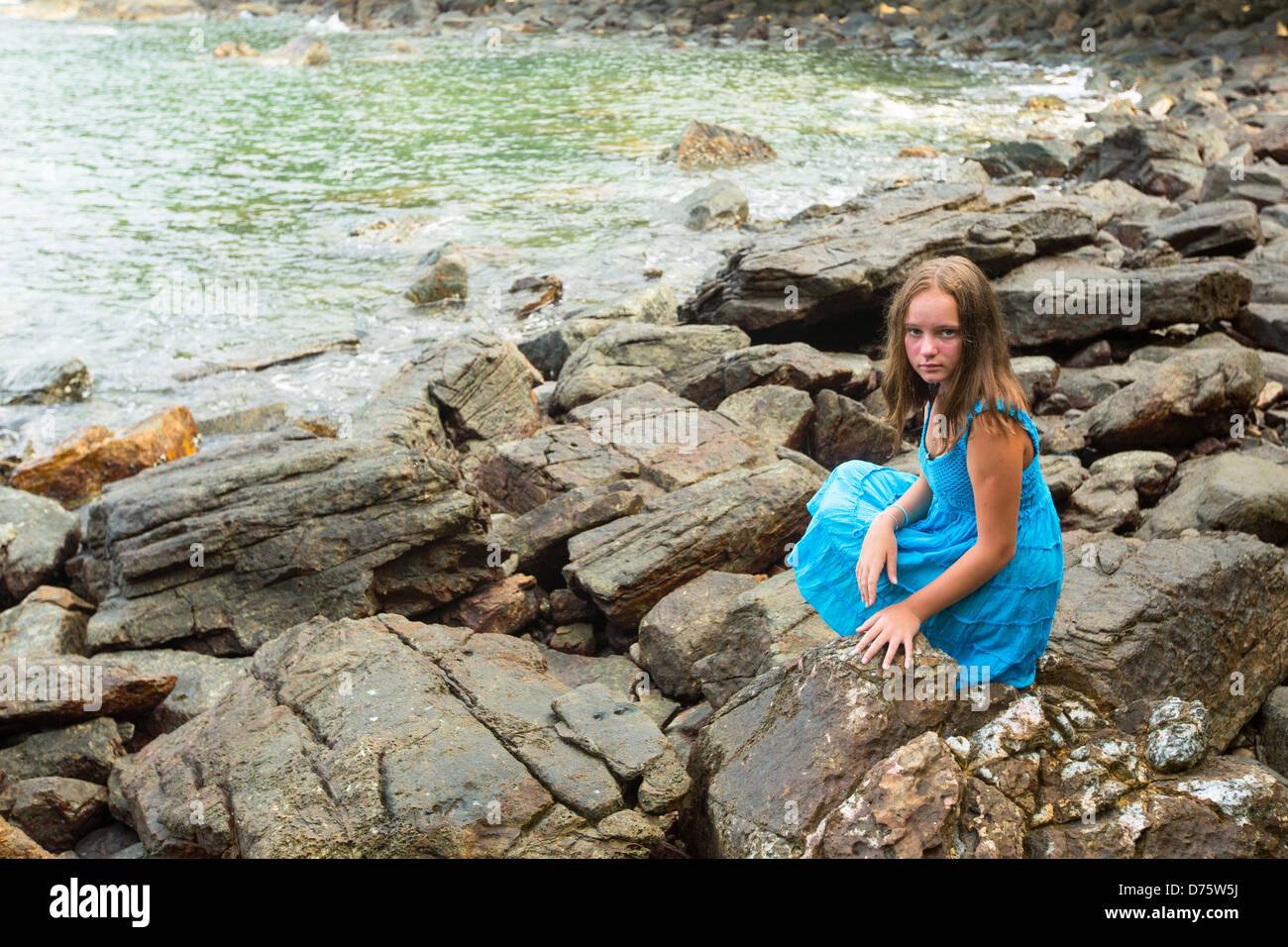 Teen-Mädchen in einem blauen Kleid in den Felsen der Küste. Stockbild