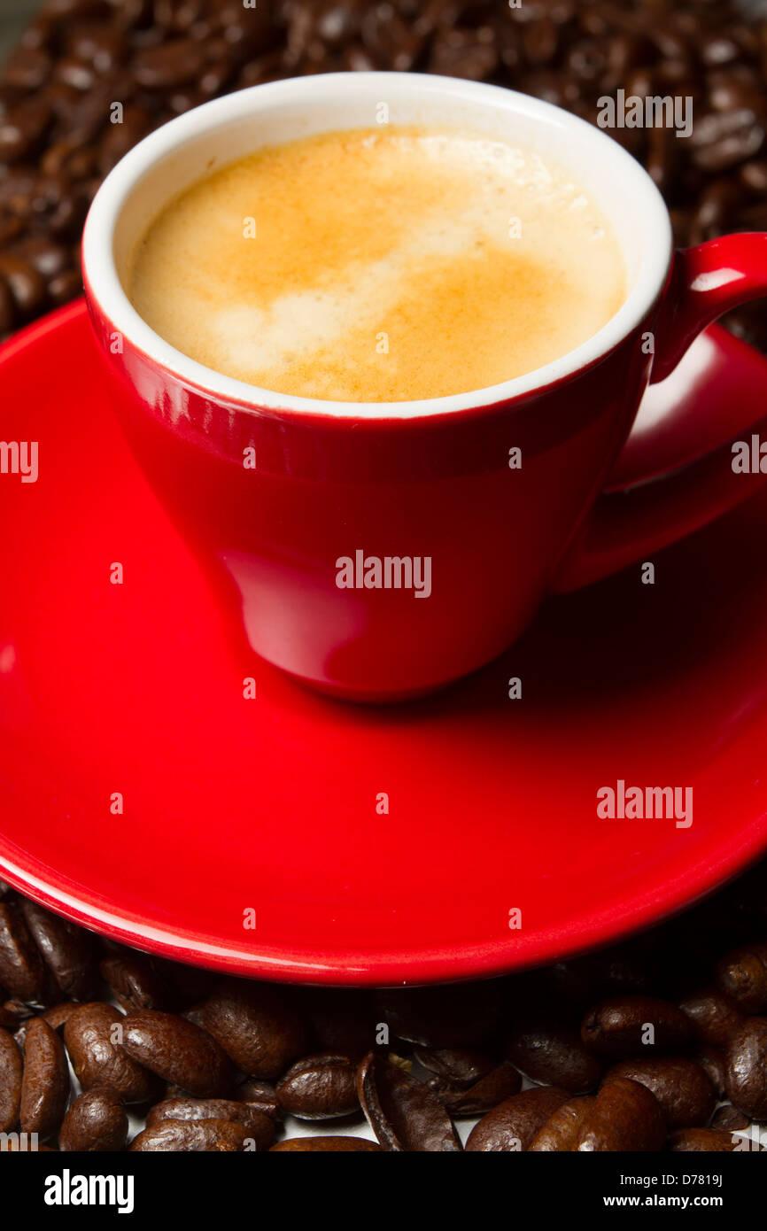 Espresso-Kaffeemaschine in einem roten Tasse und Untertasse mit frischen ganzen Kaffeebohnen in den Hintergrund, Stockbild