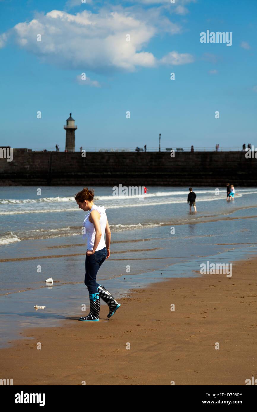 Junge Dame in Gummistiefel auf Whitby Strand, Yorkshire, UK, England Stockbild