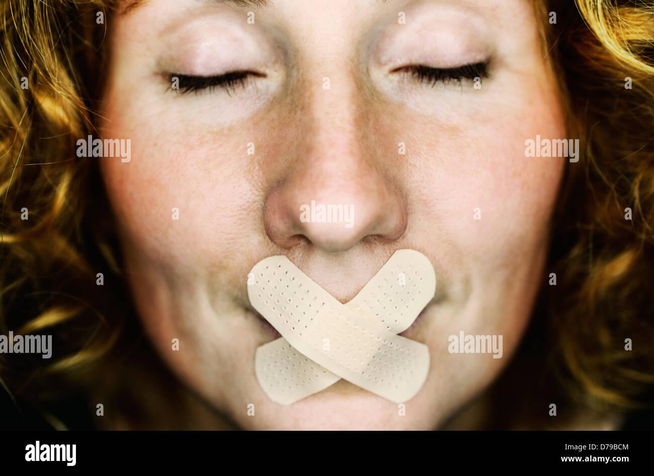Frau mit Pflaster auf den Mund, symbolische Foto Rede Verbot, Frau Mit Pflaster Auf Dem Mund, Symbolfoto Redeverbot Stockbild