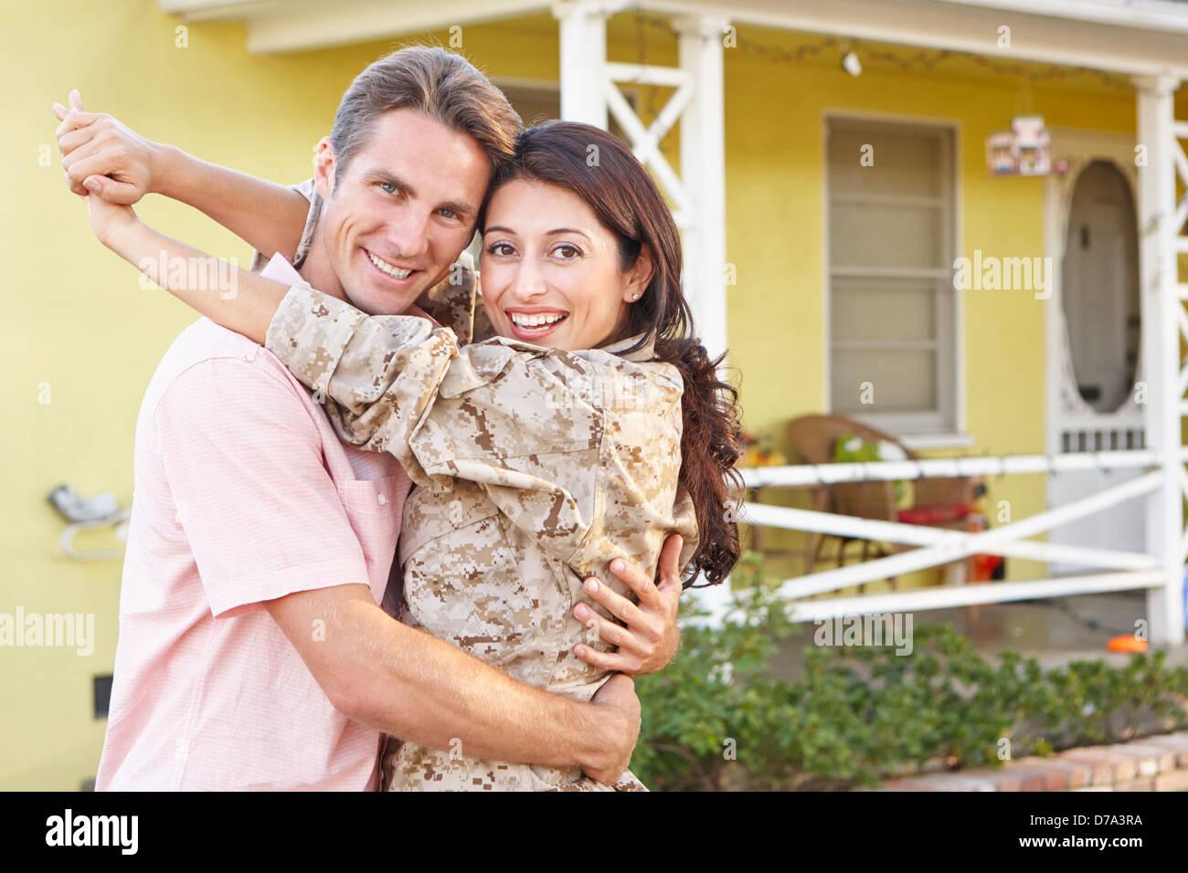Mann, die Frau Zuhause Armee beurlaubt begrüßen Stockbild