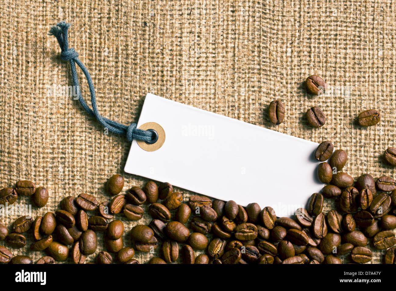 Kaffeebohnen und Preisschild auf Sackleinen Stockbild