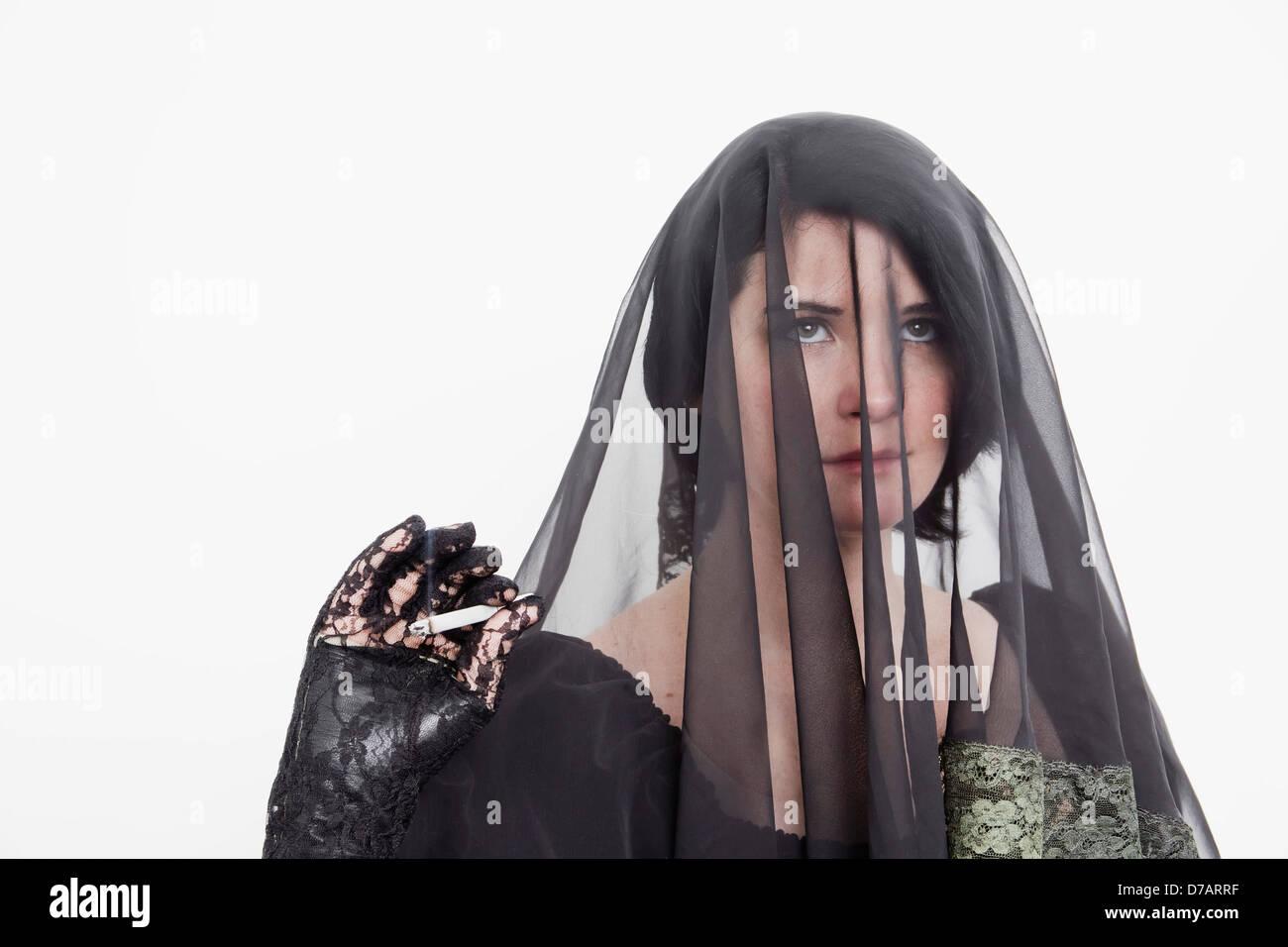 Junge verschleierte Frau mit einer Zigarette. Stockbild