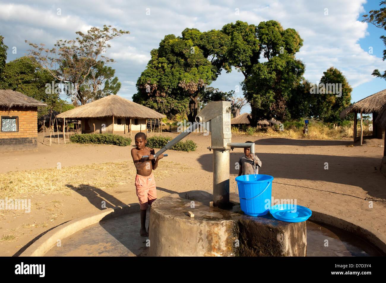Junge Pumpen von Wasser aus einem Brunnen, See Niassa, Mosambik Stockbild