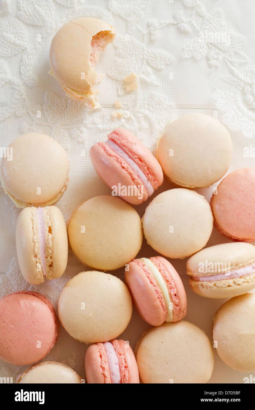 Ein Haufen französische Mandel Macarons auf weißem Holz und Spitze, Teil einer Serie. Stockbild