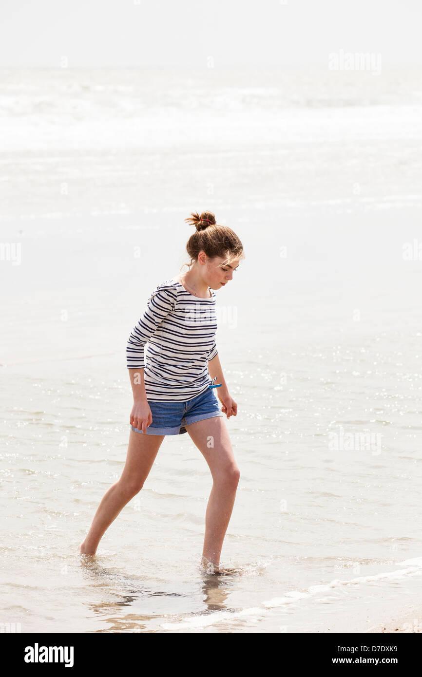 Mädchen, waten im Wasser am Strand Stockbild
