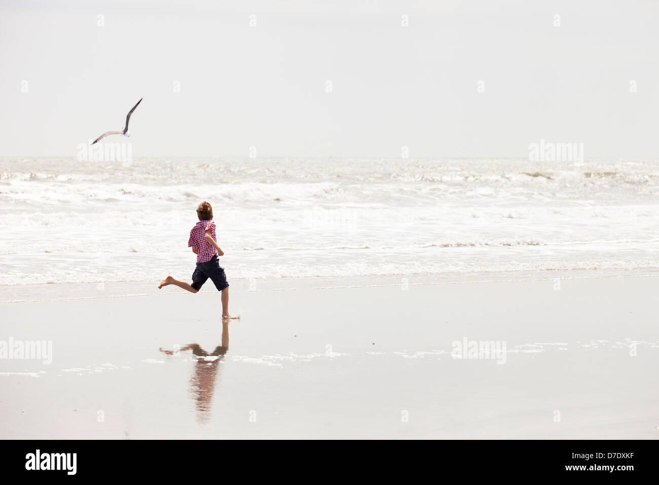 Junge am Strand laufen Stockbild