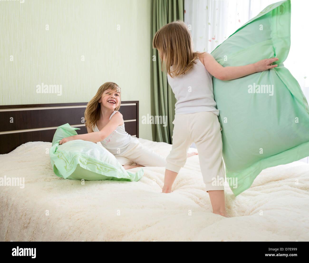 zwei Mädchen spielen mit Kissen im Schlafzimmer Stockbild