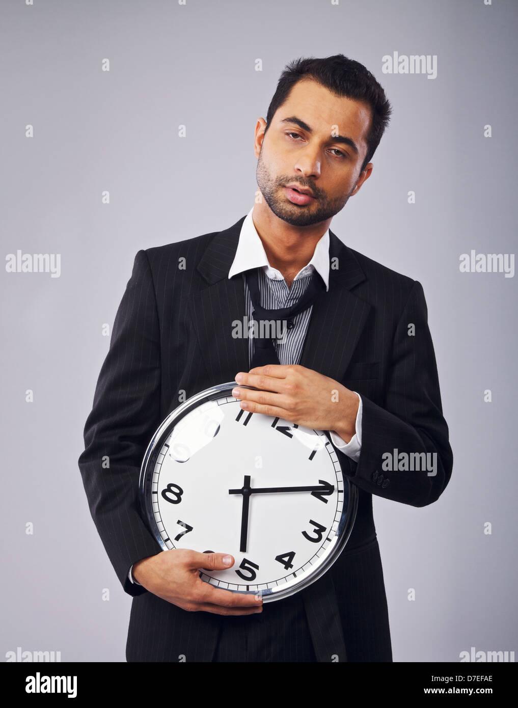 Verschlafene Büroangestellte hält eine Uhr Stockbild