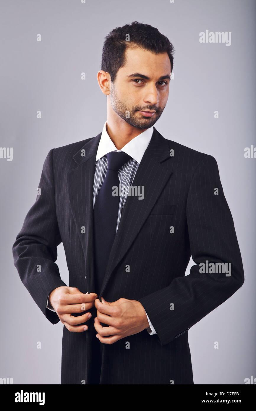 Junge Manager betrachten Sie während knöpfte seinen Anzug Stockbild