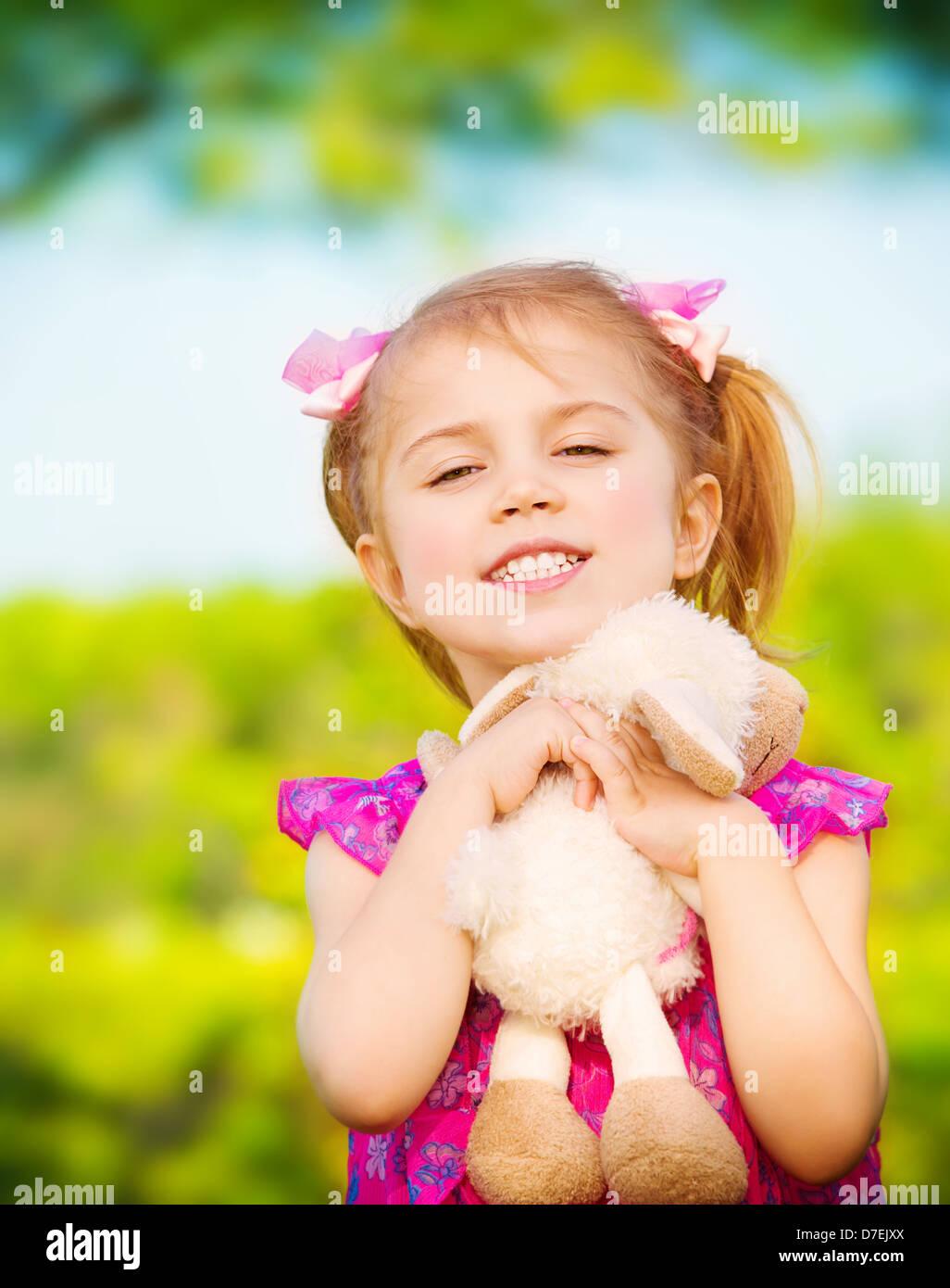 Süßes kleines Mädchen umarmen Stofftier im Freien im Frühling, Rollenspiel auf Hinterhof, Tagespflege, Stockbild