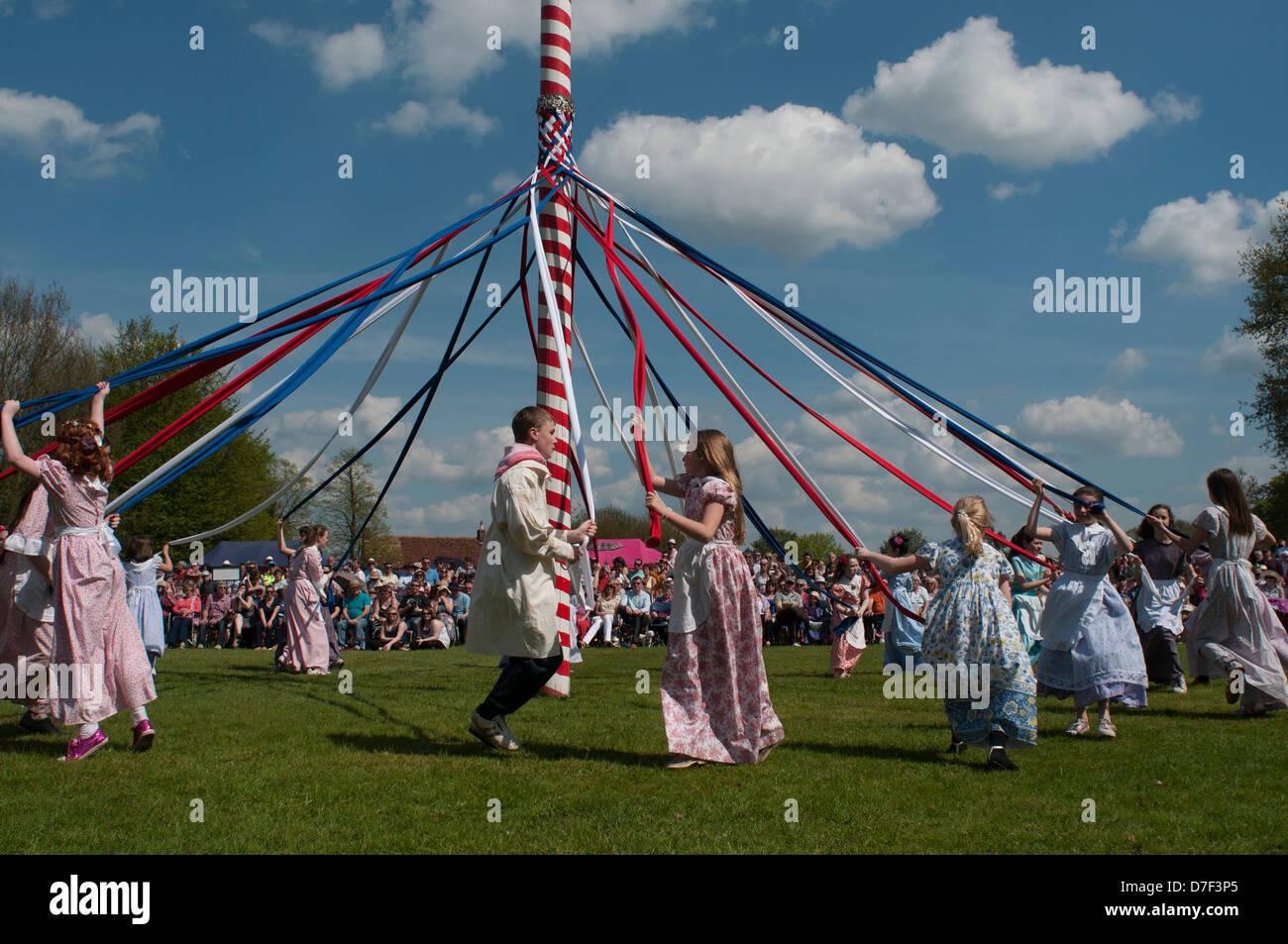 Maibaum Tanz, Ickwell, Bedfordshire, England, Mai 2013. Kinder tanzen um den Maibaum auf dem Dorfplatz in Ickwell. Stockbild