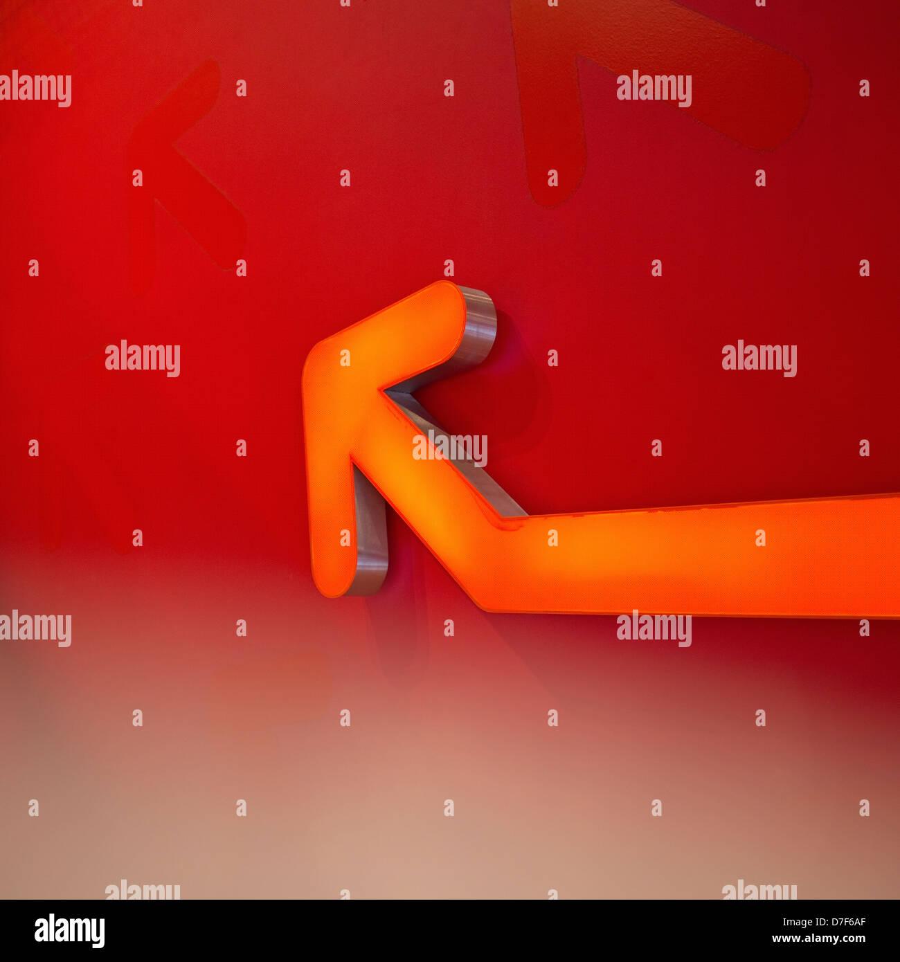Ein orange Neon Pfeil zeigt die Richtung nach oben auf eine andere Ebene Stockbild