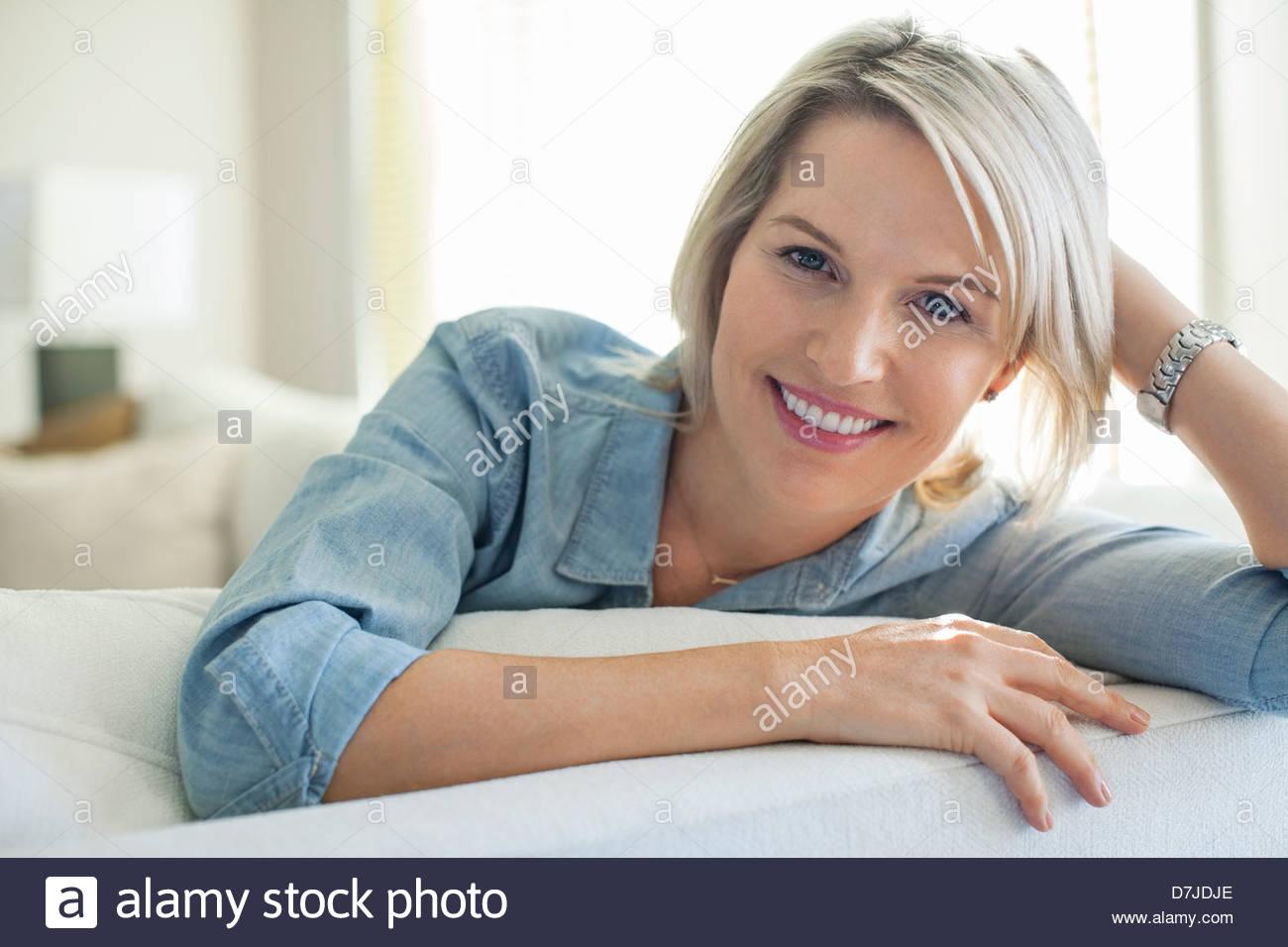 Porträt der lächelnde Frau entspannend auf sofa Stockbild