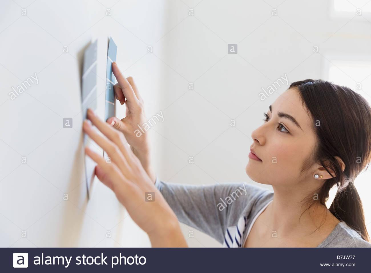 Junge Frau, die Auswahl der Farbenfarben zu Hause Stockbild
