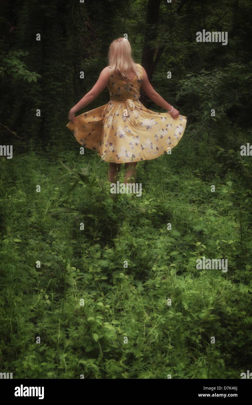 eine blonde Mädchen mit einem gelben Kleid tanzt im Wald Stockbild