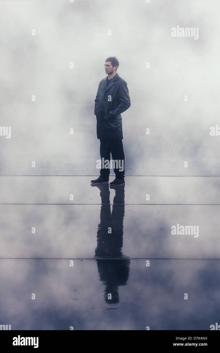 ein finsterer Mann in einer schwarzen nass Lederjacke bei Regen Stockbild