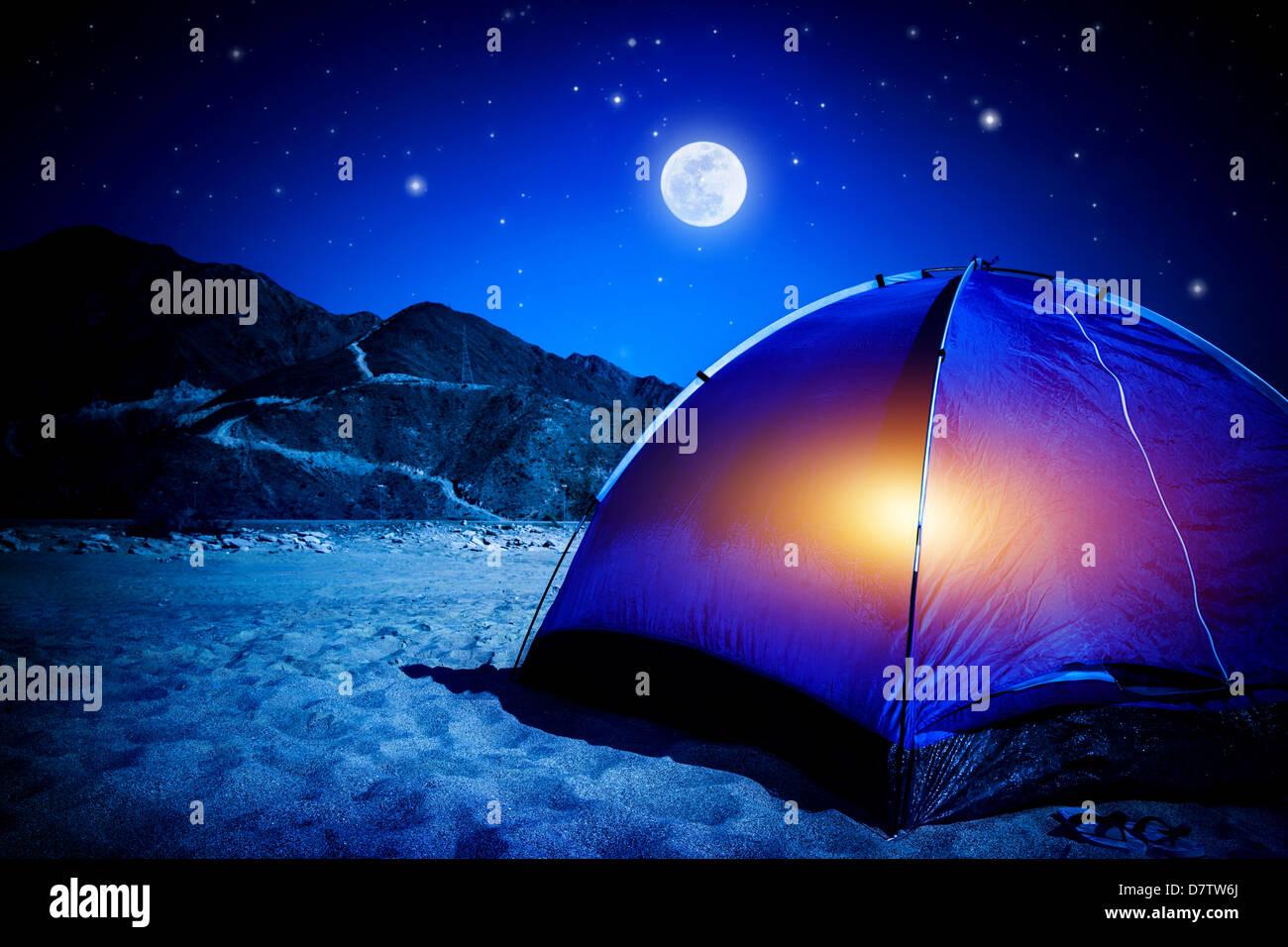 Camp am Sandstrand, Zelt nachts mit Licht im Inneren, Mondlicht, Aktivurlaub, Wandern und Reisen Konzept Stockbild