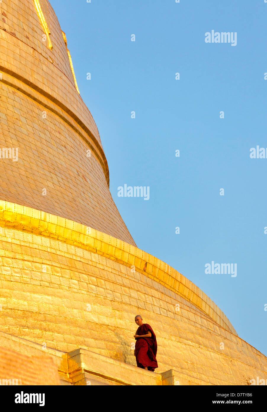 Buddhistischer Mönch zu Fuß rund um die vergoldete Kuppel der Shwedagon Paya (Pagode) in der Abenddämmerung, Stockbild
