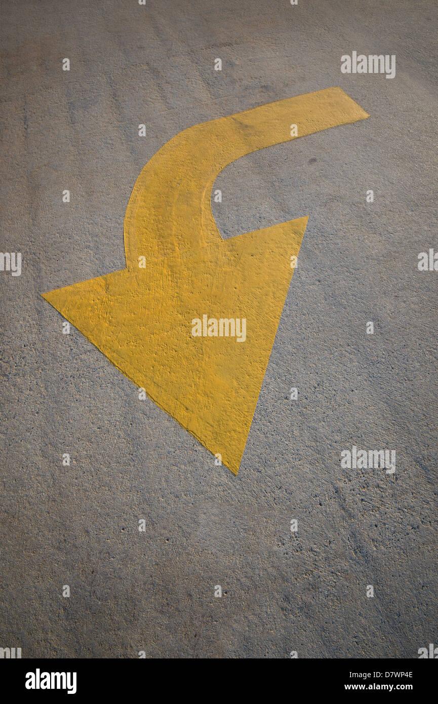 Gebogener gelber Pfeil auf Zement gemalt Stockbild
