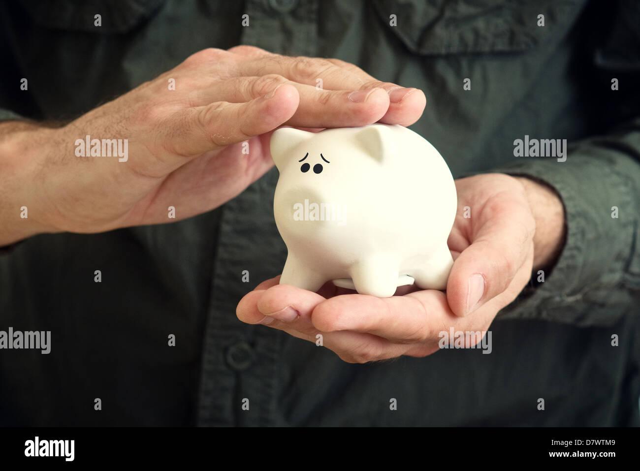 Hand schmiegt weißen Piggy Spardose mit Angst Blick in seine Augen. Stockbild
