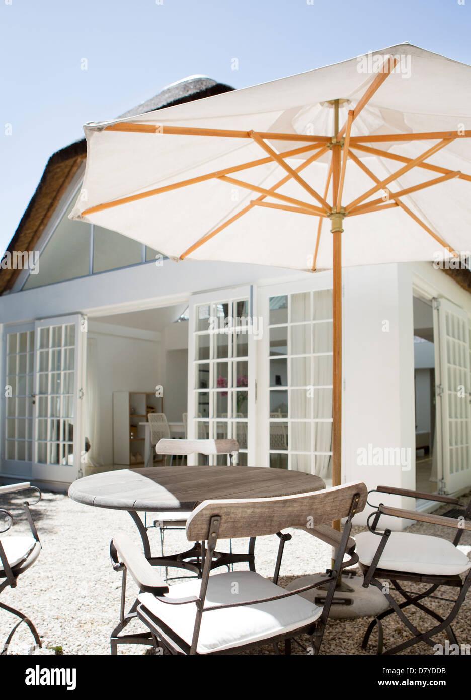 Regenschirm über Tisch im Hinterhof Stockbild
