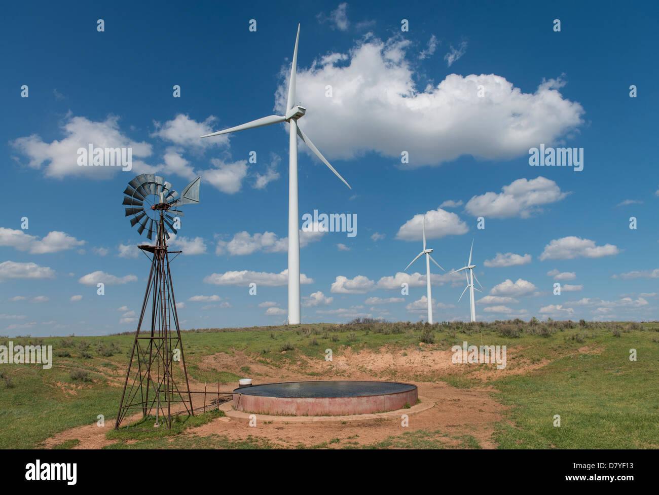 Eine alte Windmühle zur Wasserförderung sitzt neben Windmühlen zur Stromerzeugung im Nordwesten Oklahoma Stockbild