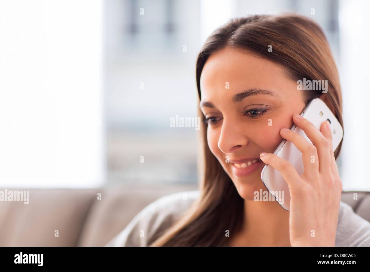 Hübsche junge Frau mit weißen Handy zu Hause Stockbild