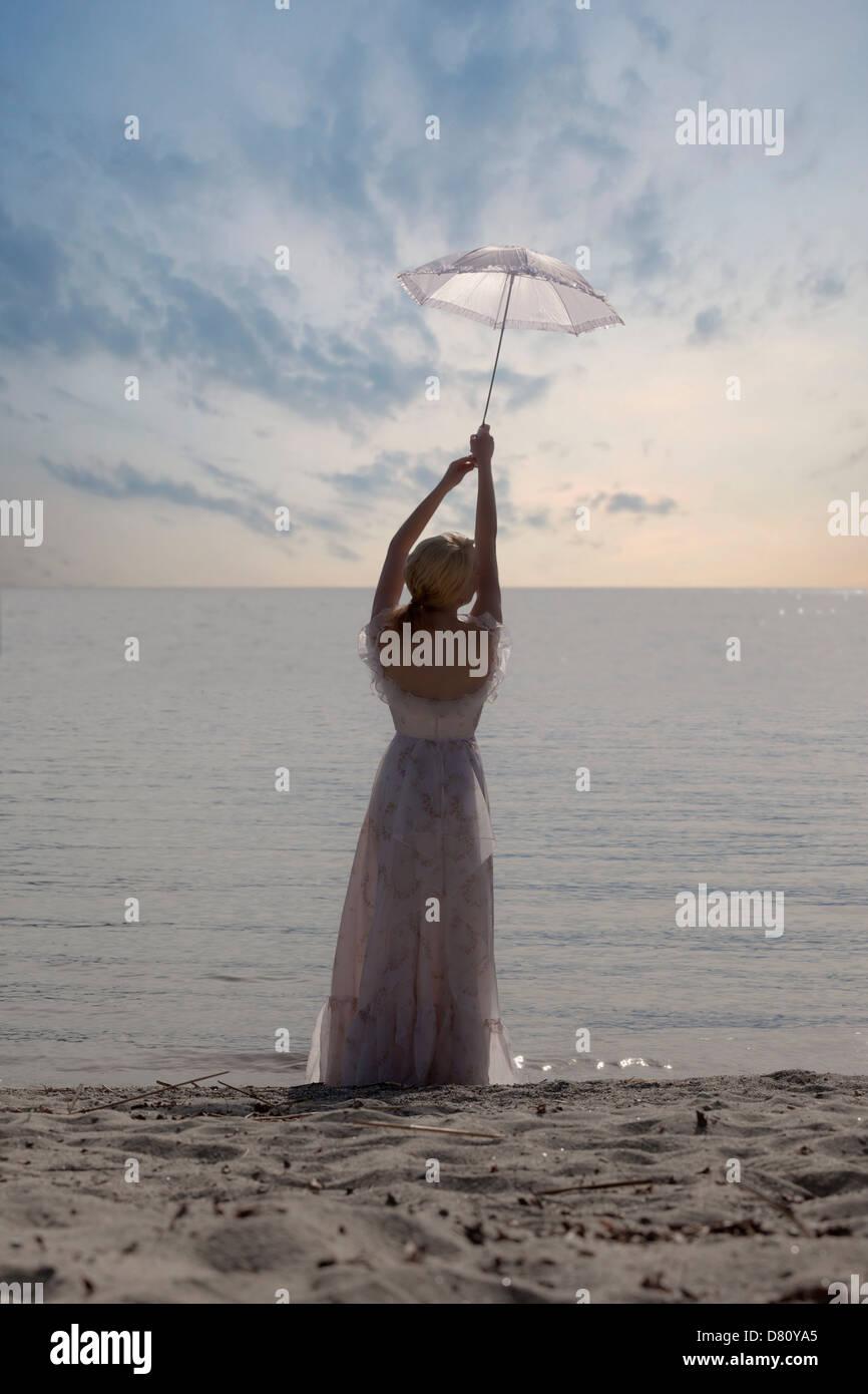 eine Frau am Strand mit einem weißen Sonnenschirm Stockbild
