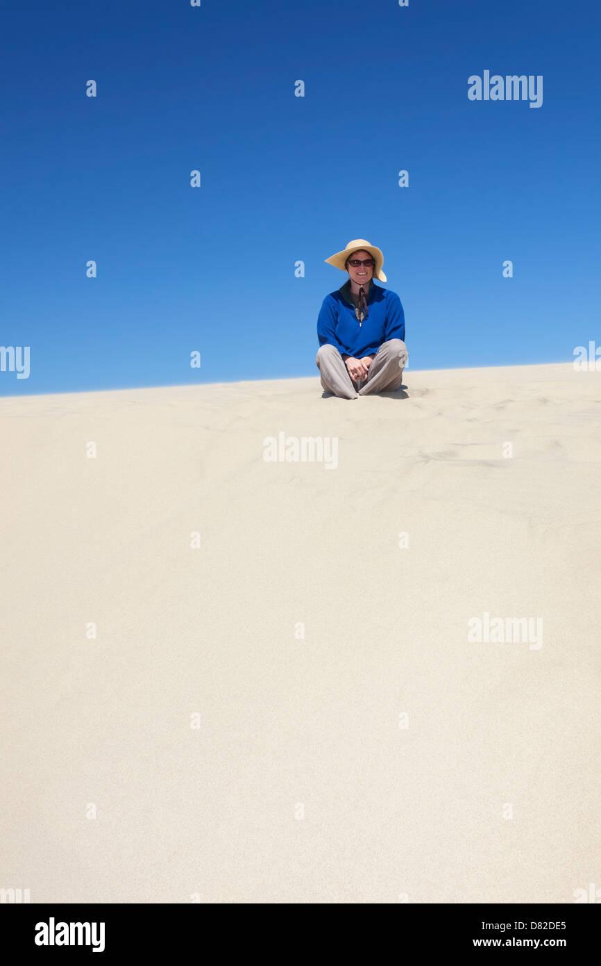 Frau mit Hut sitzt auf einer Sanddüne, Florence, Oregon Stockbild