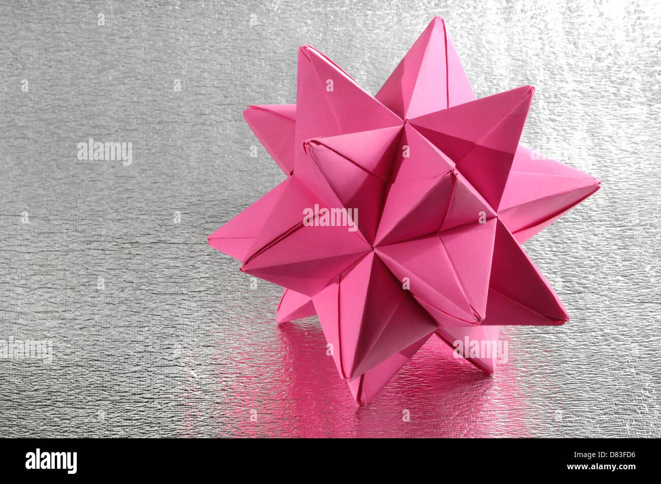 Abstrakte lila Origami Polyeder Figur auf silbernen Hintergrund Stockbild