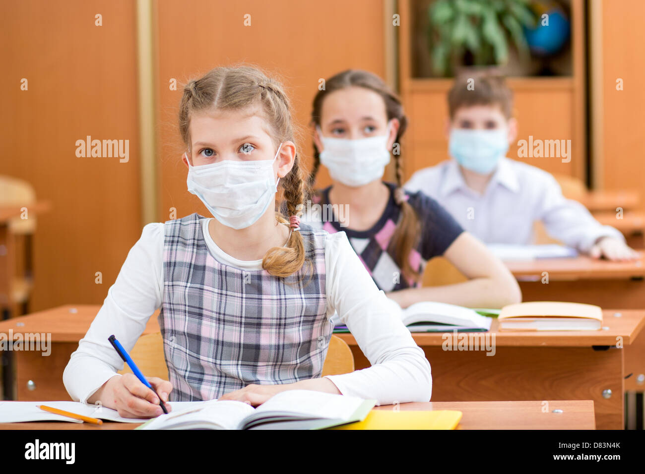 Schüler mit Maske Schutz gegen Grippe-Virus bei Lektion Stockbild