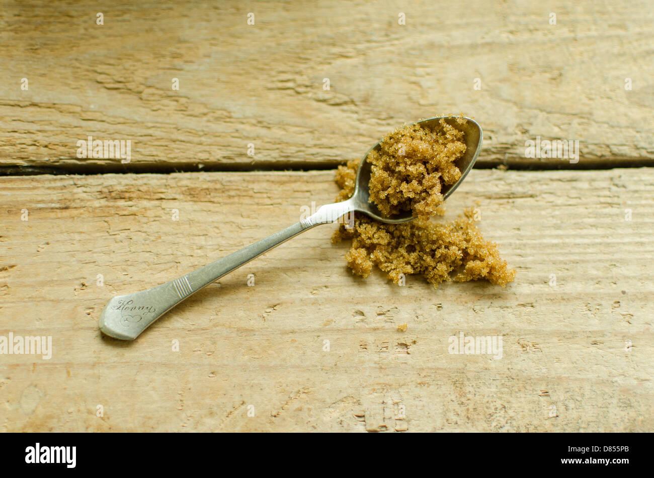 Braunem Zucker und einem silbernen Teelöffel auf einem Holztisch Stockbild