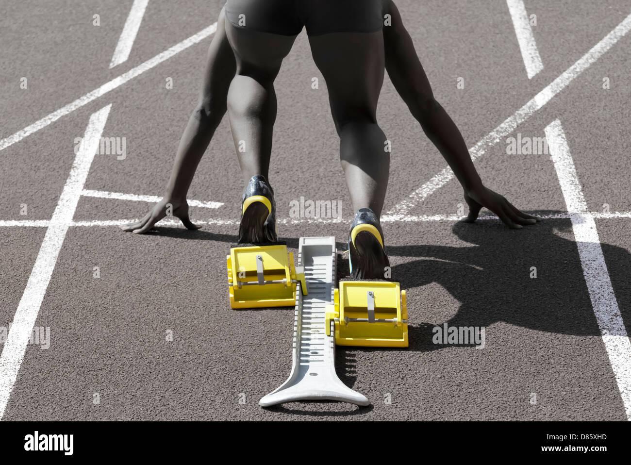 Dunkelhäutige Sprinter in Startposition vorbereitet für den start Stockbild