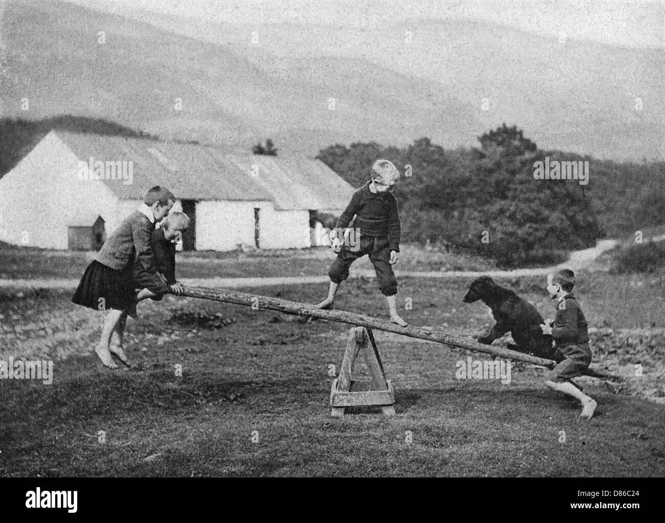 Kindern und einem Hund spielen auf einer Wippe Stockbild
