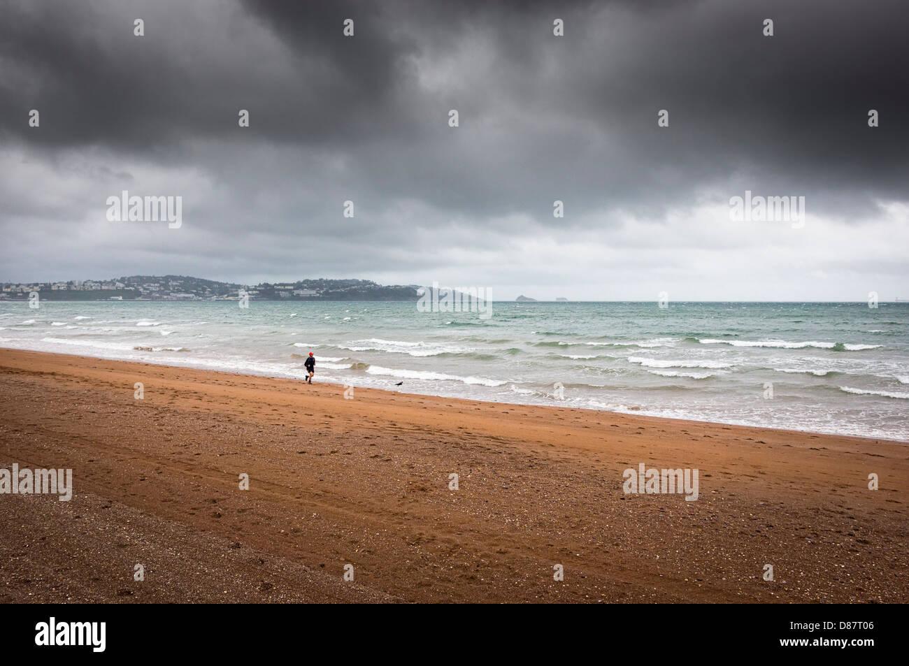 Läufer auf Paignton Beach im Regen mit Gewitterhimmel, Devon Küste, England, UK im Frühjahr/Sommer Stockbild