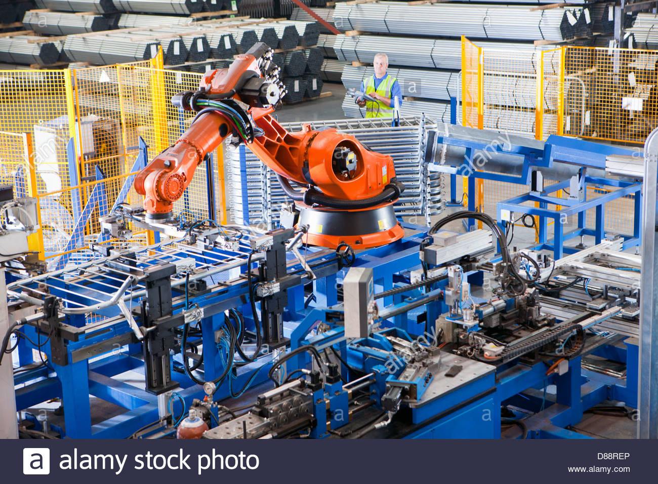 Arbeiter, die Steuerung der Roboter Maschinen heben Stahl Fechten auf Produktionslinie im Werk Stockbild