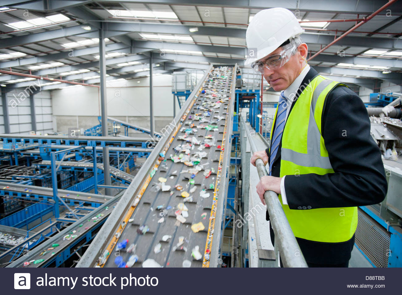 Geschäftsmann gerade Kunststoff auf Förderband in recycling-Anlage Stockbild