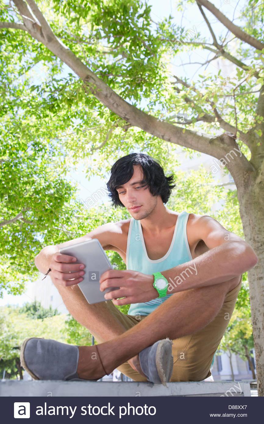Junger Mann mit digital-Tablette unter Baum im park Stockbild