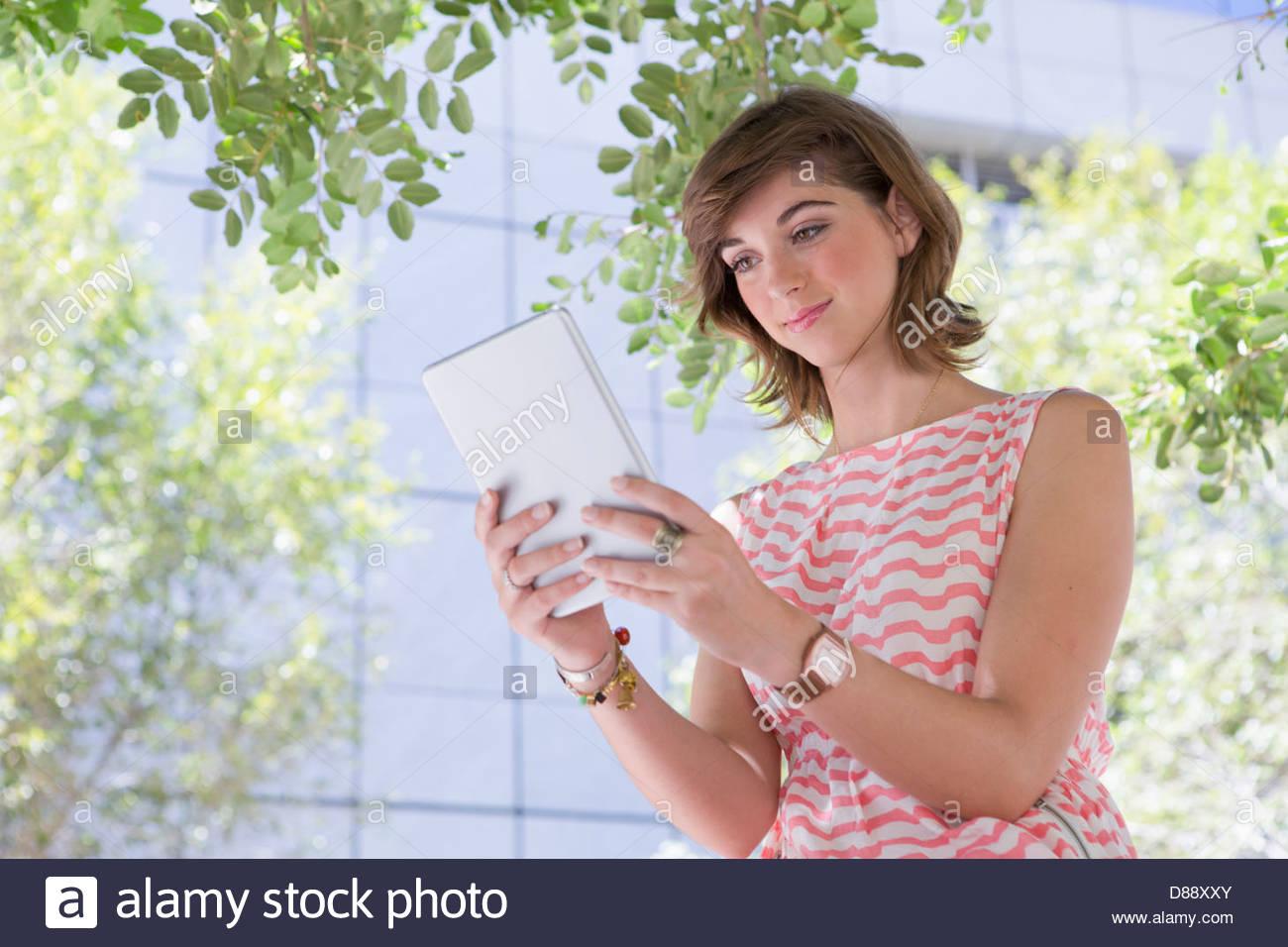 Lächelnde junge Frau mit digital-Tablette unter Baum Stockbild