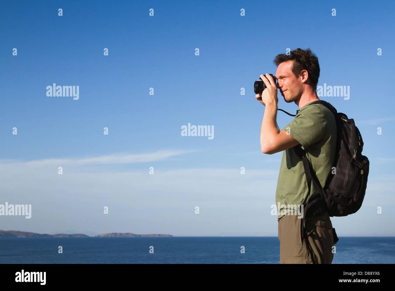 Fotograf und Reisenden mit dem Rucksack fotografieren im freien Stockbild
