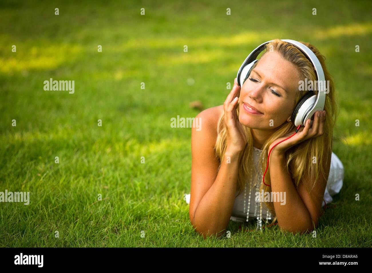 Glück-Mädchen mit Kopfhörern genießen Natur und Musik am sonnigen Tag. Stockbild