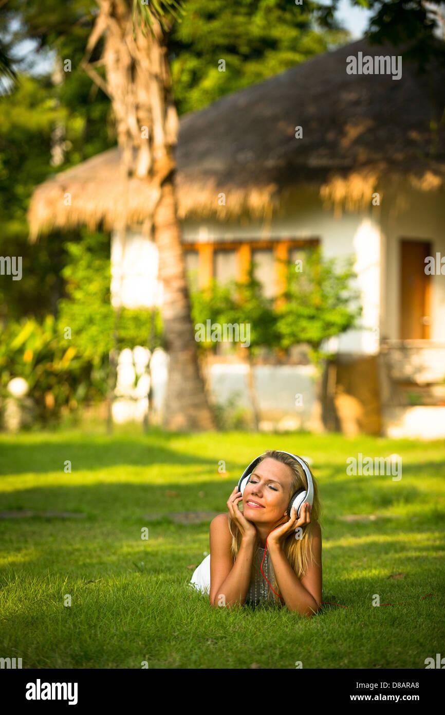 Schöne Mädchen mit Kopfhörern genießen Natur und Musik am sonnigen Tag Stockbild