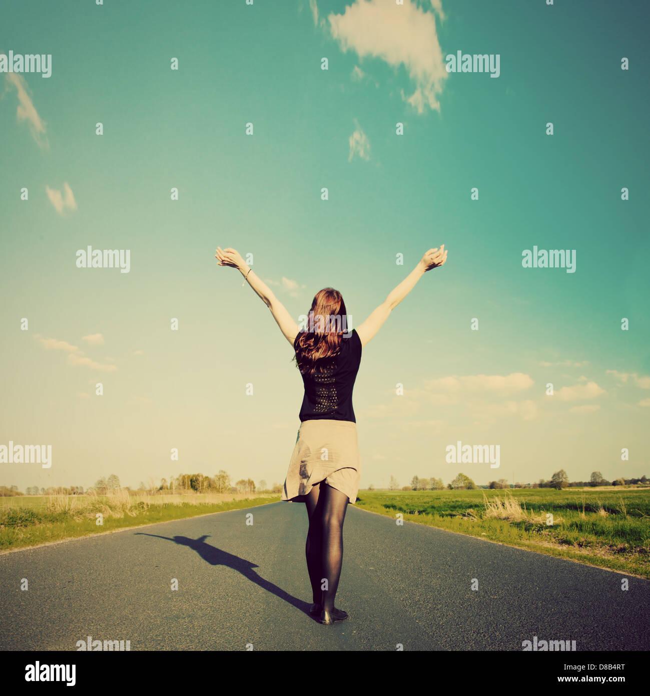 Glückliche Frau mit Händen stehend auf langen geraden Straße mit Blick auf die Sonne. Retro-Vintage Stockbild