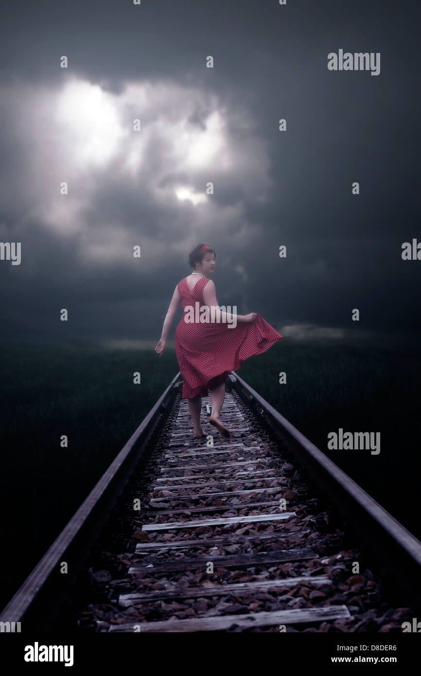 eine Mädchen in einem roten Kleid läuft auf Schienen Stockbild