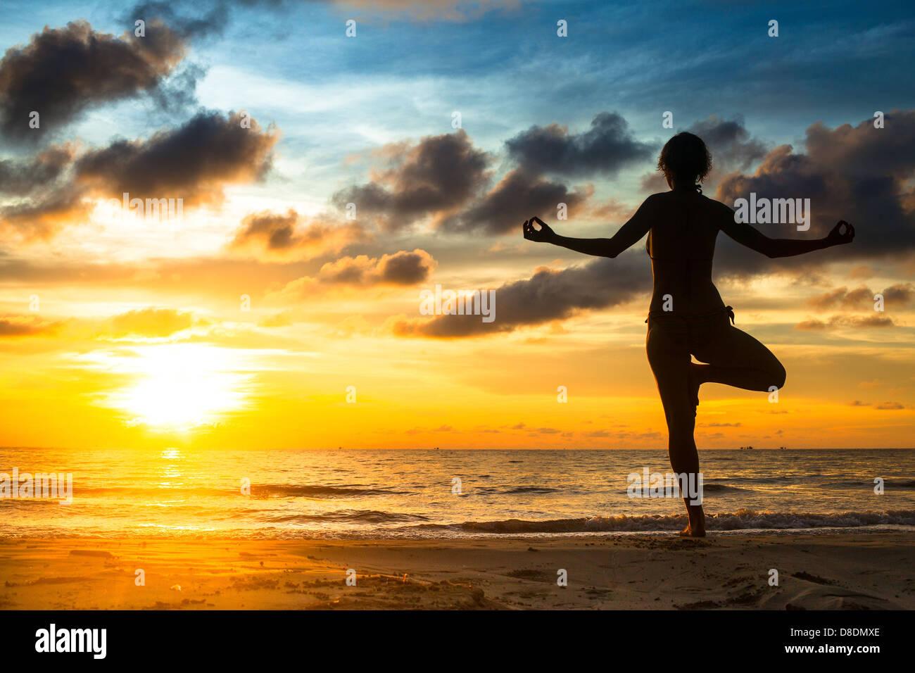 Mädchen üben Yoga am Meer bei Sonnenuntergang. Stockbild