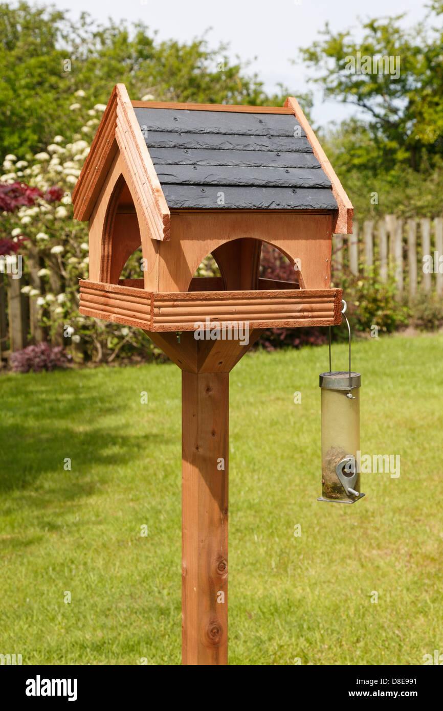 holz vogelhaus mit schieferdach und samen zubringer in einem garten im sommer uk. Black Bedroom Furniture Sets. Home Design Ideas