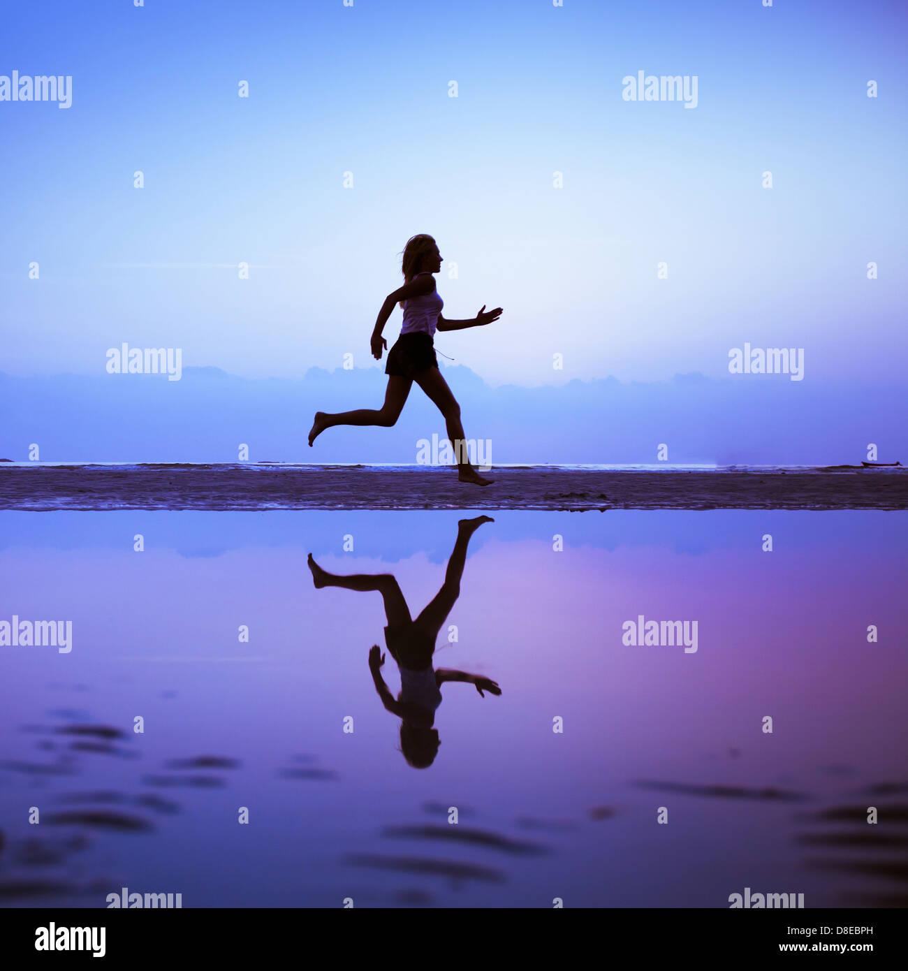 Weibliche Läufer Silhouette ist unten mit einem blauen Himmel Sonnenuntergang als Hintergrund gespiegelt. Stockbild