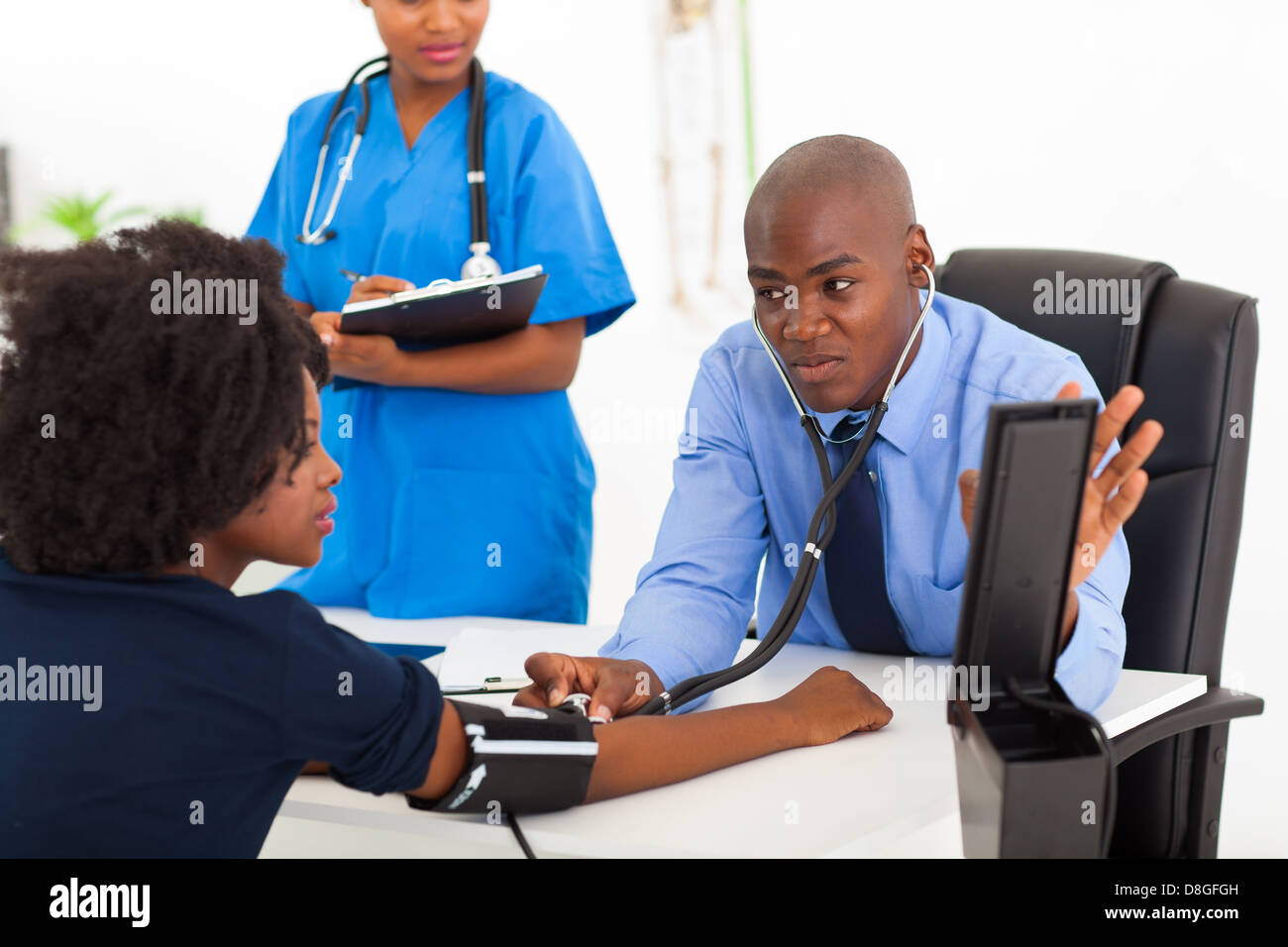 Afrikanische Allgemeinmedizin Überprüfung des Patienten Blutdruck im Büro Stockbild