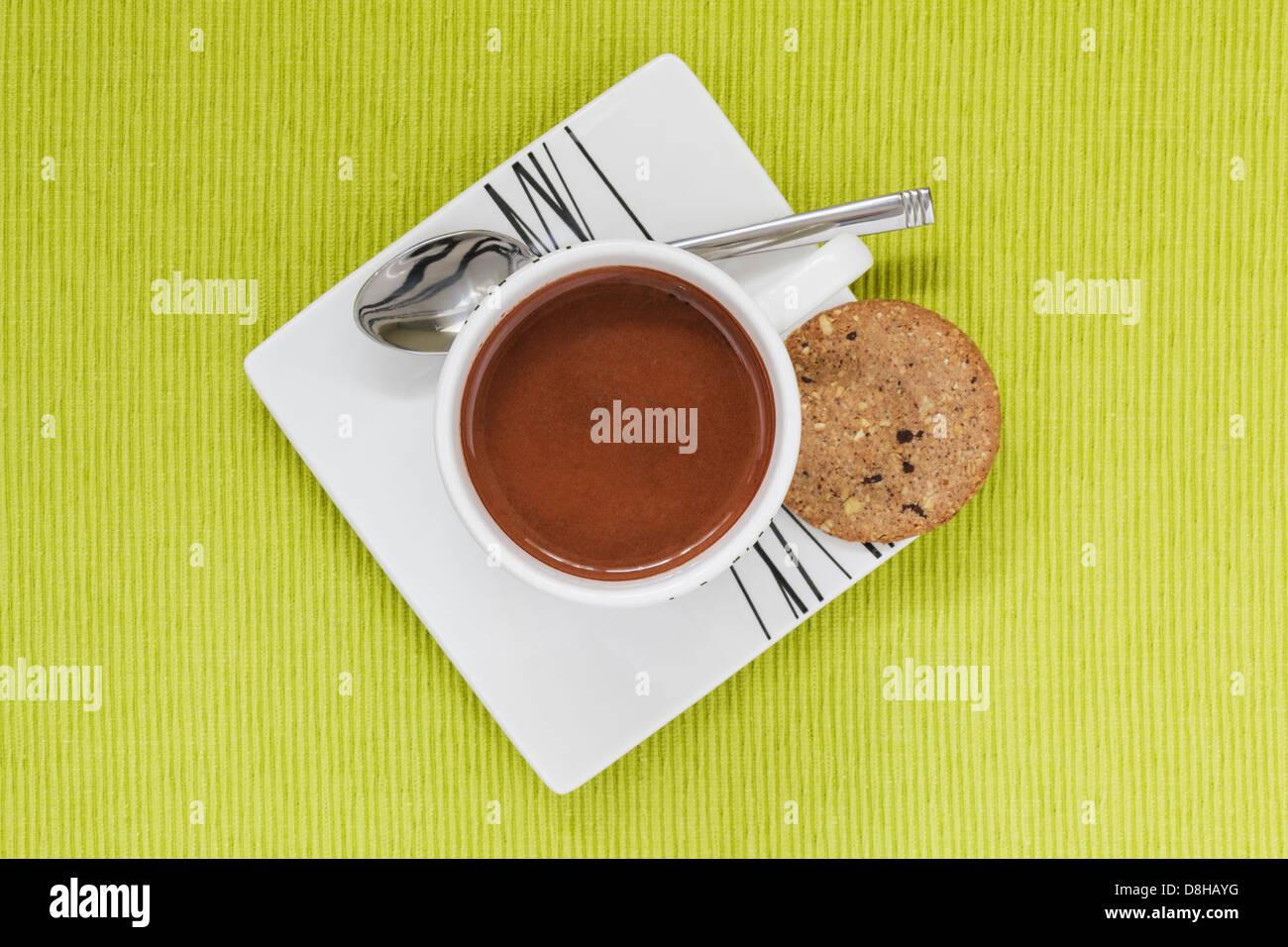 Heiße Schokolade trinken in weiße Tasse, Untertasse und Keks von oben Stockbild